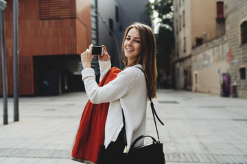 Tourist female taking photo by a mobile phone camera while exploring new city on a weekend journey. Cheerful hipster girl capturing on video on a smartphone while walking the street.
