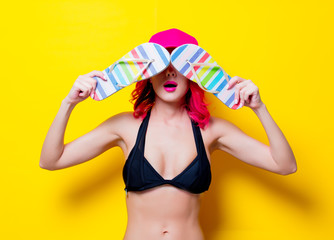 Young pink hair girl in bikini with cap and sandals. Portrait isolated on yellow background