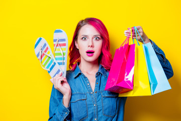 Young pink hair girl in blue shirt holding a colored shopping bags and flip flops. Portrait on isolated yellow background