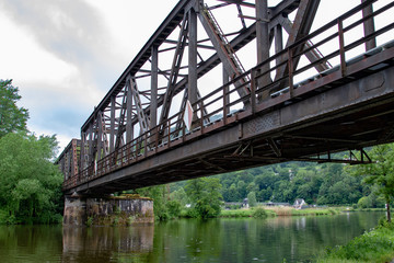 Rusty metal train bridge over a small river