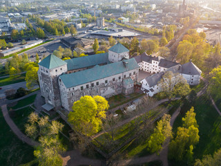 Aerial view of Turku Castle at morning sun with green springtime trees and park in Turku, Finland
