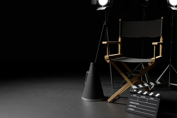 Director Chair,Megaphone,Movie Clapper and lighting equipment on dark background.