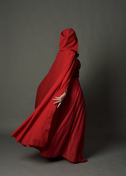 full length portrait of woman wearing red fantasy costume with cloak, standing pose on grey studio background.