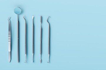 Dentist tools on pastel blue background.
