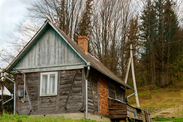 Old-fashioned wooden house on the outskirts of the forest. Among the Carpathian mountains in Ukraine. Outdoors.