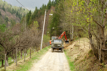 The excavator expands the road and loads the land in a truck in the mountains of the Carpathians, Ukraine. Outdoors.