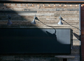 Black billboard on a wooden wall with lamps and string of lights