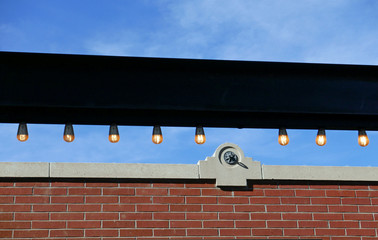 Row of lights over a brick facade