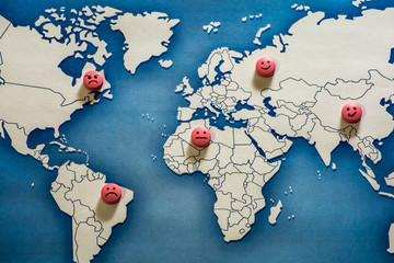 A few pills are on the political map of the world. The tablets are painted with emoticons.