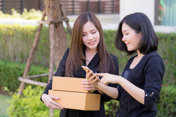 Happy Asian woman using smartphone to shop online with hand holding deliveried package