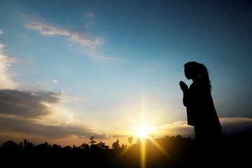 Praying and hope concept, silhouette of women pray for peach and success in life