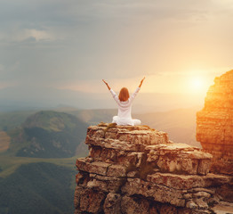 woman practices yoga and meditates   on mountains .