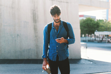 a young attractive usually dressed hipster guy with a backpack uses a e-map on modern mobile phone and holds coffee cup. a handsome guy is using a smartphone to connect to a public network wifi