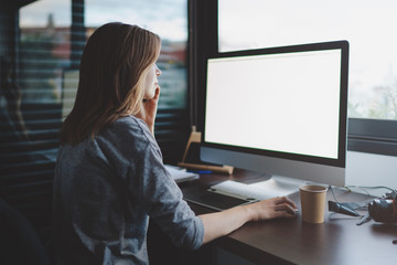 view from back to female student is talking on smartphone sitting at desk in front of monitor with blank space for design. Mockup screen with copy space. woman makes a business call Wall mural