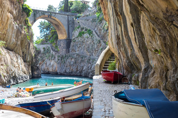 Fiordo di Furore beach. Furore Fjord Amalfi Coast Positano Naples Italy. - Fishermen colored boats on the beach, under the bridge of the fjord. The turquoise water of the beach.