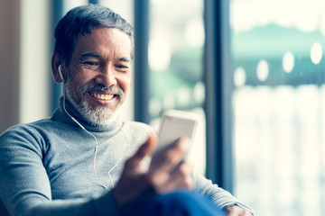Portrait Smiling Attractive mature man retired with white stylish short beard using smartphone or listening music and sitting at coffee shop cafe. Serving internet via his gadget. Old man using social