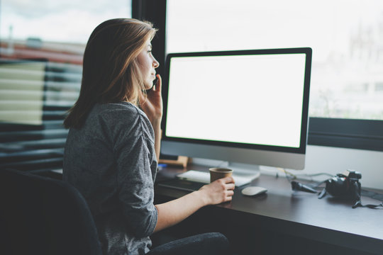 view from back to female professional entrepreneur is talking on mobile phone sitting at desk in front of monitor with blank space for design. Mockup screen with copy space.woman makes a business call