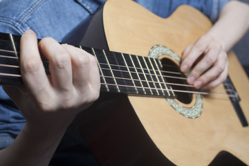 Young womans hands playing a acoustic classic guitar