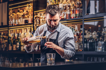 Stylish brutal barman in a shirt and apron makes a cocktail at bar counter background.