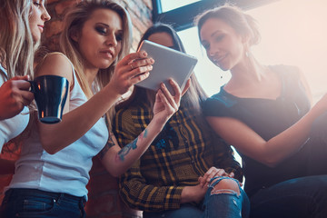 Group of female friends in casual clothes discussing while looking something on a digital tablet in a room with loft interior.