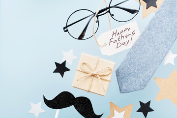 Greeting card on Happy Fathers Day with gift box, glasses, necktie and funny moustache on blue table top view in flat lay style.