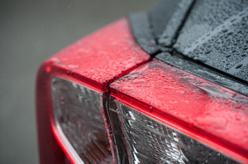 closeup of raindrops rear lights of on black car