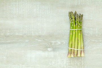 Asparagus sprouts on light wooden surface.