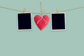 Blank instant photos and red heart hanging pastel color background.