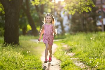 Little girl is running in the summer park