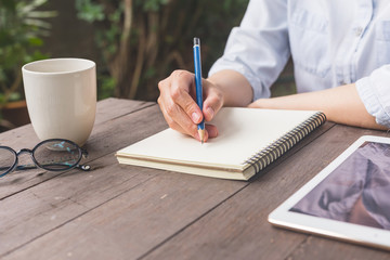 Hand woman writing notebook on wood table with cup coffe and tablet.