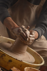 Hands of a potter, creating a ceramic pot on the pottery wheel