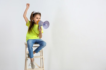Cute little girl with megaphone sitting against white background