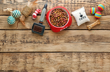 Cat's accessories and food on wooden background