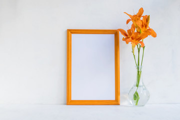 Mockup with a golden frame and orange summer flowers