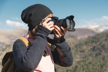 Close-up portrait of a blond girl with a digital SLR camera photographing in the mountains. Stylish freelancer photographer with backpack in mountain caucasian trip