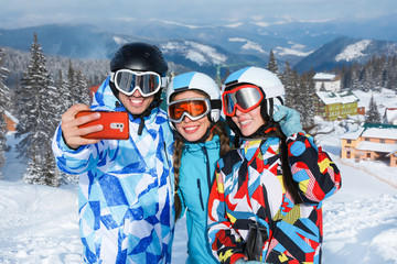 Group of friends taking selfie at snowy ski resort. Winter vacation