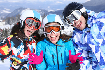 Group of happy friends at snowy ski resort. Winter vacation