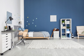 Modern child room interior with comfortable bed and desk