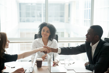 Smiling african businessman handshaking greeting caucasian businesswoman at group meeting negotiation, black satisfied entrepreneur welcoming partner shaking hand in lawyers office, respect concept