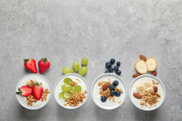 Bowls with yogurt, granola and different fruits on gray background, top view