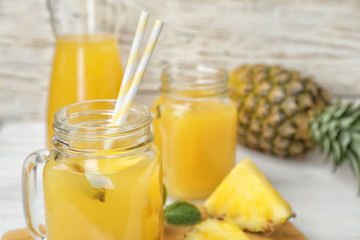 Mason jars with delicious pineapple juice on table
