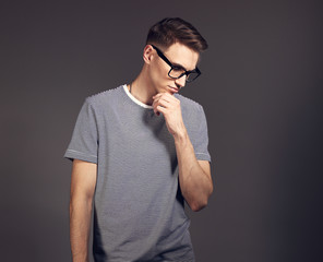 Fashion thinking man posing in trendy glasses and looking down in strip casual shirt on grey background. Toned closeup portrait