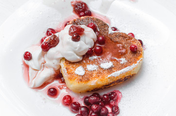 Freshly baked curd on the plate with cranberry and powdered sugar and sour cream on white wooden table background.