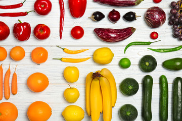 Rainbow composition with fresh vegetables and fruits on wooden background, flat lay