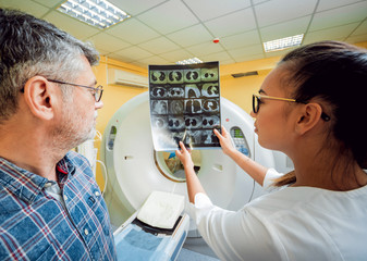 Radiologist with an male patient looking at x-ray.