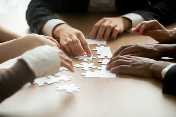 Finding best business solutions and teamwork concept, multiracial team assembling puzzle on office desk engaging in decision making and teambuilding, close up view of diverse hands connecting pieces