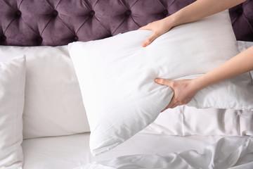 Young woman making bed, closeup