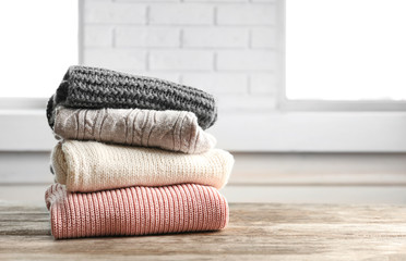 Fototapete - Stack of warm knitted clothes on table