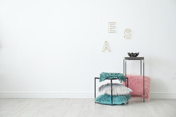 Tables with pillows near white wall in room