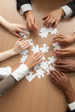 Multiracial team assembling puzzle together, hands of diverse people connecting pieces engaging in finding solutions, teambuilding and teamwork concept, business help support, close up vertical view